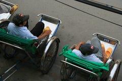 Riksjabestuurders in een straat in Hoi An (Vietnam) Stock Foto's