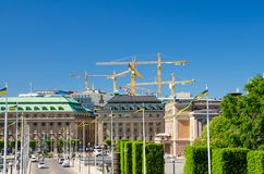 Riksplan, bushes and street with national flags on Sodermalm island, Gustav Adolfs torg square, Royal Swedish Opera house building royalty free stock images