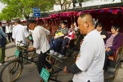 Riksza odtransportowywają pasażerów przy Futong ulicą obok Houhai jeziora w Pekin, Chiny Obraz Stock