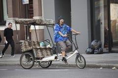 Riksza w błękitnej koszula i okularach przeciwsłonecznych jedzie wokoło miasta w poszukiwaniu klientów Fotografia Royalty Free