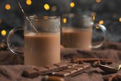 Rikt övervintra varm choklad med kanelbruna pinnar, och valnötter, chokladstänger i ett genomskinligt rånar på ett träbräde, sele royaltyfri bild