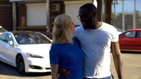 Rikt blandras- omfamna för par som står mot den lyxiga bilen, hyra för automatisk royaltyfri fotografi