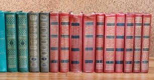 Rikt dekorerade volymer av böcker med en guld- bokstäver royaltyfri bild
