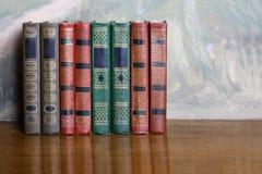 Rikt dekorerade volymer av böcker med en guld- bokstäver royaltyfri foto