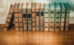 Rikt dekorerade volymer av böcker med en guld- bokstäver på bet arkivfoto