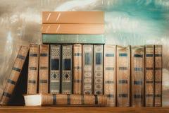 Rikt dekorerade volymer av böcker med en guld- bokstäver på bet arkivbild
