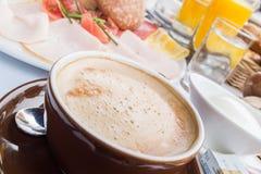 Rikt dold europeisk frukosttabell med kaffe, bröd, ägg och orange fruktsaft royaltyfri foto