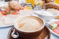 Rikt dold europeisk frukosttabell med kaffe, bröd, ägg och orange fruktsaft royaltyfri fotografi