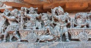 Rikt indiskt folk som reser med hästvagnar, på väggen med gammal lättnad hinduisk Hoysaleshwara för 12th århundrade tempel i Indi Fotografering för Bildbyråer