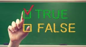 RIKTIG eller FALSK checkbox med handen arkivfoto