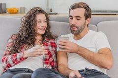 riktig förälskelse Gladlynta romantiska par som sitter på soffan i ett hemtrevligt rum och le arkivfoton