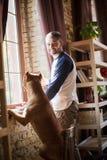 Riktiga vänner, man och hans hund som hemma spenderar tid Royaltyfri Foto