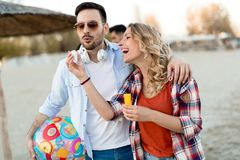 Riktigt lyckliga skämtsamma par som har gyckel på stranden royaltyfri bild