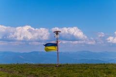 Riktningstecken med den ukrainska flaggan överst av det gröna berget Royaltyfri Fotografi