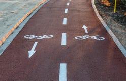 Riktningstecken som målas på golvet av en cykelgränd royaltyfri fotografi