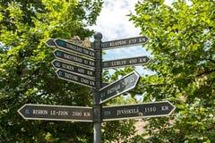 Riktningstecknet indikerar avstånd till olika städer Fotografering för Bildbyråer