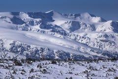 积雪覆盖的峰顶冬天视图在Rila山的 免版税图库摄影