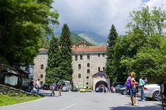Eople near the entrance arch of in Unesco World Heritage site famous Rila Monastery, Rilsky monastery. RILA, BULGARIA - JUN 29, 2014: People near the entrance stock images