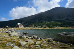Rila mountain. Landscape with blue sky and clouds and a rest house near lake Royalty Free Stock Photo