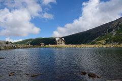 Rila mountain. Landscape with blue sky and clouds and a rest house near lake Stock Photo