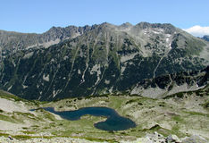 Rila mountains in Bulgaria, deep blue lakes and gray rock summit during the sunny day with clear blue sky Stock Images