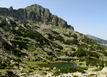 Rila mountains in Bulgaria, deep blue lakes and gray rock summit during the sunny day with clear blue sky Stock Photos
