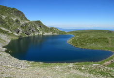 Rila mountains in Bulgaria, deep blue lakes and gray rock summit during the sunny day with clear blue sky Stock Image