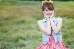 Rilassamento biondo grazioso della ragazza all'aperto in erba verde Immagini Stock Libere da Diritti