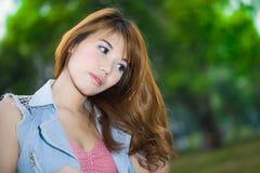 Rilassamento biondo grazioso della ragazza all'aperto in erba verde Fotografie Stock
