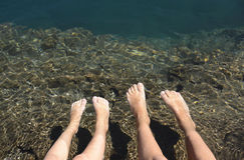 Rilassamento dei piedi nel lago immagini stock libere da diritti