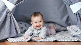 Rilassamento di menzogne sorridente del piccolo bambino adorabile a casa avendo foto a figura intera positiva di emozione stock footage