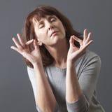 Rilassamento di zen per meditare donna splendida 50s Fotografia Stock