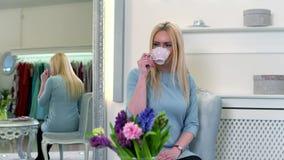 Rilassamento femminile biondo grazioso con il caffè che si siede vicino allo specchio in boutique di lusso video d archivio