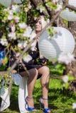 Rilassamento femminile biondo sensuale nella foresta di primavera su oscillazione Wh enorme Immagine Stock