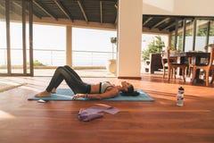 Rilassamento femminile sul pavimento dopo l'allenamento Fotografia Stock