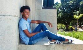 Rilassamento giovane africano felice dell'adulto all'aperto Immagini Stock