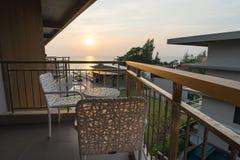 Rilassamento mentre tramonto alla sedia del balcone Fotografia Stock
