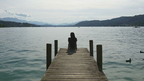 Rilassamento nel lago della montagna La donna si siede sul bacino stock footage