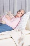 Rilassamento senior femminile attivo sullo strato Fotografia Stock Libera da Diritti