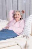 Rilassamento senior femminile attivo sullo strato Fotografia Stock