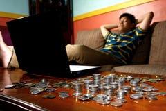Rilassamento teenager asiatico davanti al computer portatile e ad una pila di monete Fotografie Stock