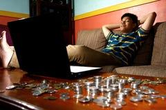 Rilassamento teenager asiatico davanti al computer portatile e ad una pila di monete Fotografia Stock Libera da Diritti