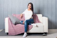 Rilassandosi a casa, comodità sorridere sveglio della giovane donna, rilassantesi sullo strato bianco, sofà Fotografia Stock