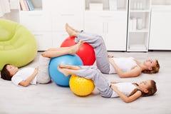 Rilassandosi dopo l'allenamento - donna e bambini che riposano sul pavimento Immagine Stock