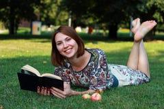 Rilassandosi in natura con il libro Fotografia Stock