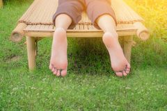 Rilassandosi sul banco di bambù nel sole di estate Fotografia Stock