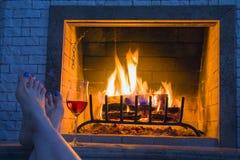 Rilassi al camino domestico bruciante - gambe femminili e un bicchiere di vino fotografia stock