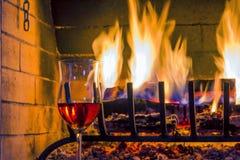 Rilassi al camino domestico bruciante, un bicchiere di vino fotografia stock