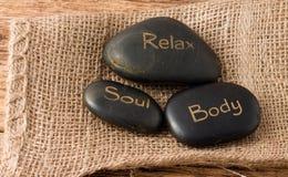Rilassi, anima, pietre della lava del corpo tre sul panno della iuta Fotografia Stock