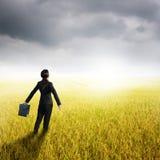 Rilassi la borsa della tenuta della donna di affari nel giacimento e nei rainclouds gialli del riso Fotografie Stock Libere da Diritti